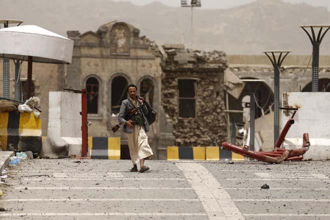 Yemen'in başkenti Sana'da Suudi bombalarıyla enkaza dönen Savunma Bakanlığı önünde bir Hutsi militan.