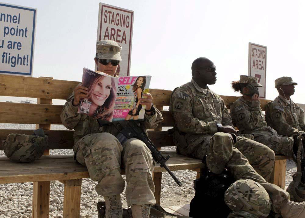 Afganistan'ındaki Kandahar üssünde, kendilerini diğer üsse transfer edecek helikopteri bekleyen ABD askeri Norma Gonzalez, bu boş vaktini dergi okuyarak değerlendiriyor.