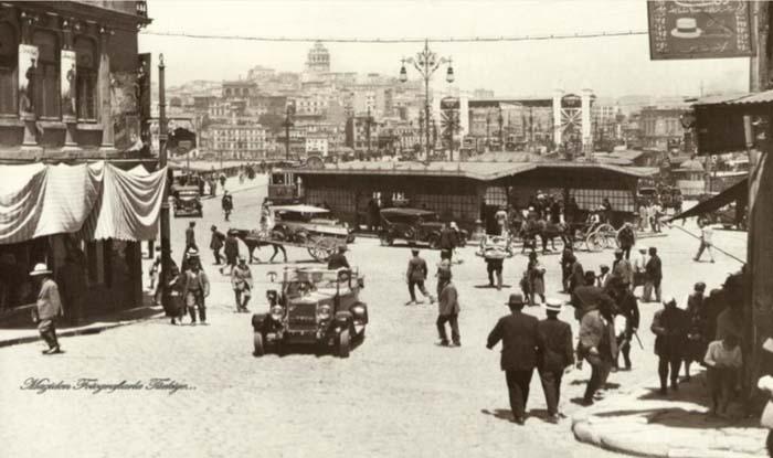 Yeni Cami basamaklarından 1928 yılında Eminönü... Bugünle kıyaslanırsa eğer, neredeyse hiç insan yok denebilir ortalıkta. Trafik belli bir doğaçlama ile akıyor… İnsanlar, 20'lerin otomobilleri, at arabaları... Kimi o tarafa kimi bu tarafa çevirm