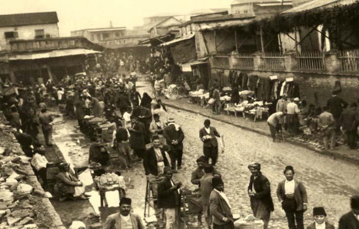 Bir çarşı sokağı... Bugünün pazarları gibi sağlı sollu yerleşmiş satıcılar...