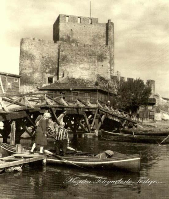 Önde yıkık dökük tahta bir iskele. Öyle yıkık dökük ki kayığa binmek üzere olan kadının iskelenin ucuna kadar nasıl yürüdüğü bile bir muamma… Arkada bir ahşap köprü, sağdaki soldaki evlerde ahşap. En arkada da taş kesmiş Anadoluhisarı... Yıl:1928… Bi